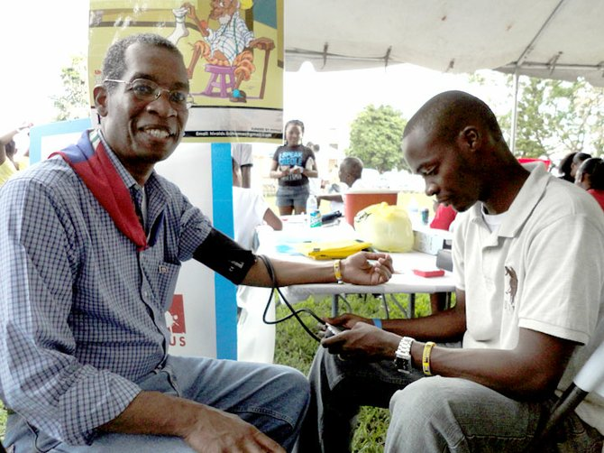 Haitian Ambassador Antonio Rodrigue (left) has his blood pressure checked on site by a Ministry of Health nurse.