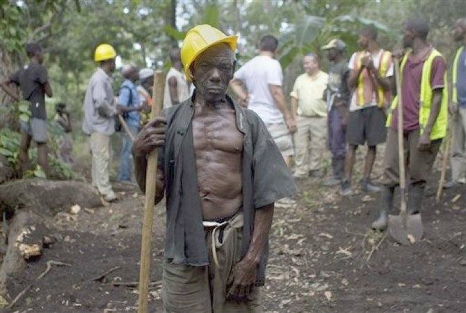 In this April 10, 2012 photo, Genove Valcimon, 70, poses for a picture as he works on a road being built through the mountains to lead to an exploratory drill site in the department of Trou Du Nord, Haiti. (AP)
