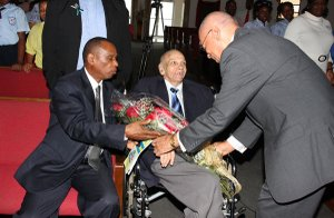 "Governor General His Excellency Sir Arthur Foulkes presents William ""Bill"" Cartwright with a bouquet of flowers during a tribute to Mr Cartwright at Chapel On The Hill, held November 1, 2011. (BIS photo/Letisha Henderson)"