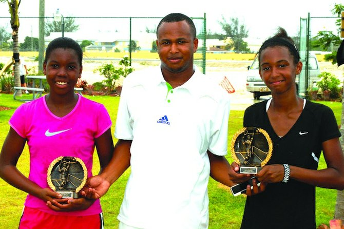 14S WINNERS: BLTA president Derron Donaldson presents the awards to the ITF Junkanoo Bowl doubles champions Gabriela Donaldson (right) and Iesha Shepherd. The duo defeated the team of Kianah Motosono and Eva Frazzoni 6-2, 4-6, 6-3 in a three-set thriller.