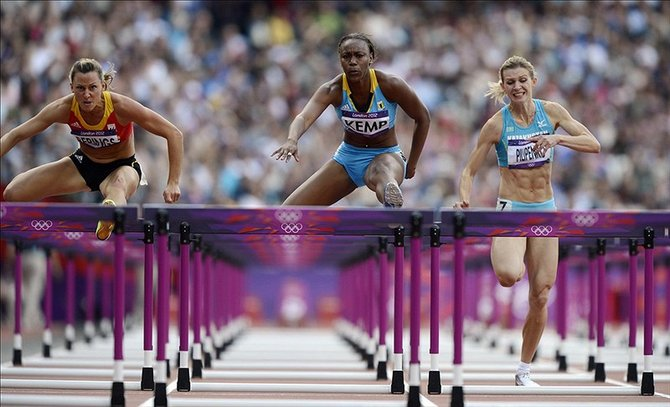 Ivanique Kemp (BAH), middle, competes in the women's 100m hurdles heats during the 2012 London Olympic Games at Olympic Stadium. Robert Deutsch-USA TODAY Sports
