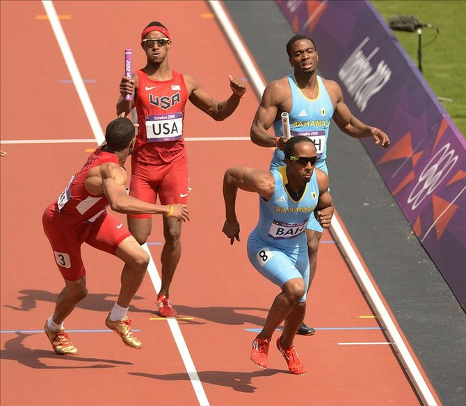 Tony McQuay (USA) and Michael Mathieu (BAH) hand off to Bryshon Nellum (USA) and Chris Brown (BAH) in the men's 4x400m heats during the London 2012 Olympic Games at Olympic Stadium. John David Mercer-USA TODAY Sports