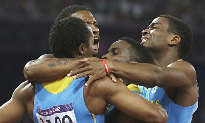 GOLDEN MOMENT: Bahamas' men's 4x400-meter relay team members Chris Brown, Demetrius Pinder, Michael Mathieu and Ramon Miller celebrate their victory during the athletics in the Olympic Stadium at the 2012 Summer Olympics, London, Friday, Aug. 10, 2012.