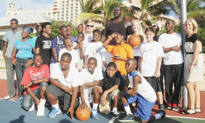 Shaquille O'Neal takes pictures with children at the basketball court at Atlantis Saturday afternoon.