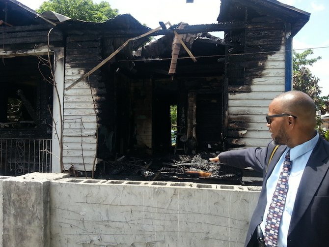 Rodney Moncur points at the remains of his home.