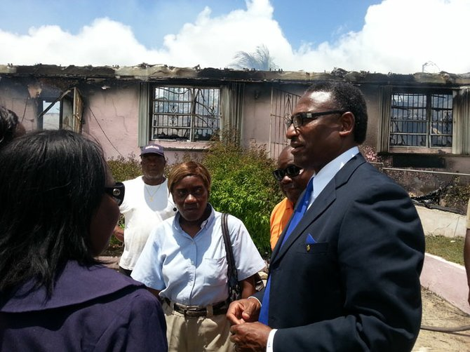 Minister of Local Government V Alfred Gray at the remains of the complex.