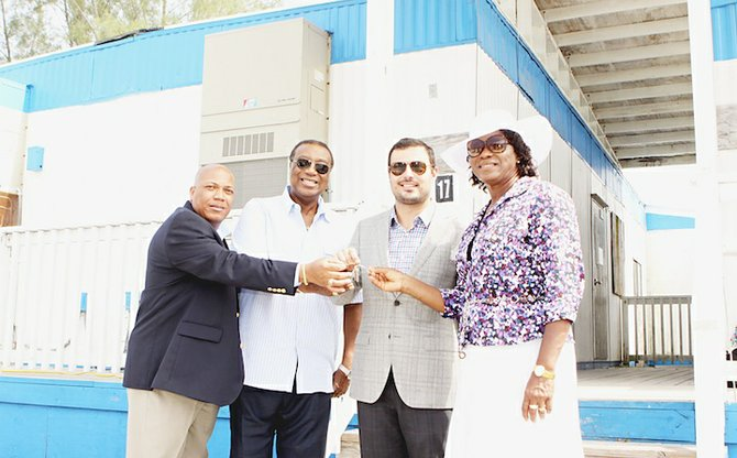 """Pictured from left: Godfrey Toote, Algernon Allen, co-chair; Mike Maierle, construction manager; and Cynthia """"Mother"""" Pratt, co-chair, receiving the keys to five office trailers being presented to Urban Renewal.  Photo: Patrick Hanna/BIS"""