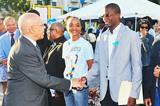 Governor General Sir Arthur Foulkes shakes the hand of an 'Autism Speaks' participant