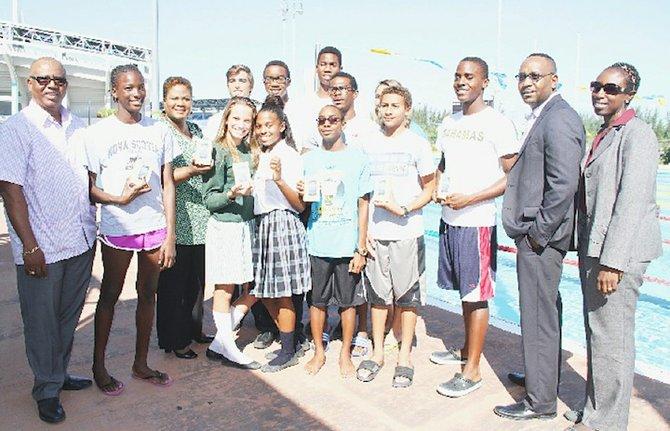 WINNING THE GOLD: Shown are Algernon Cargill (far left), Carol Barnett (3rd from left), Jerome Sawyer and Zelda Allen (far right) with some members of the CARIFTA swim team yesterday.