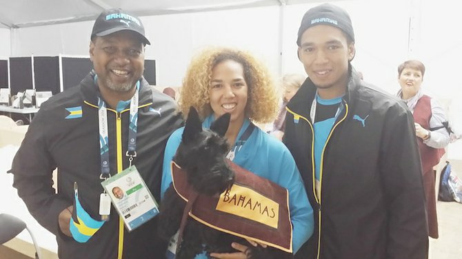 The Rahming family, comprising of father D'Arcy Sr, Cynthia and D'Arcy Jr. pose above with the Scottish Terrier that carried the Bahamas name during the Athletes March Pass at the opening ceremonies of the 20th Commonwealth Games on Wednesday night at the famous Celtic Park in Glasgow, Scotland.