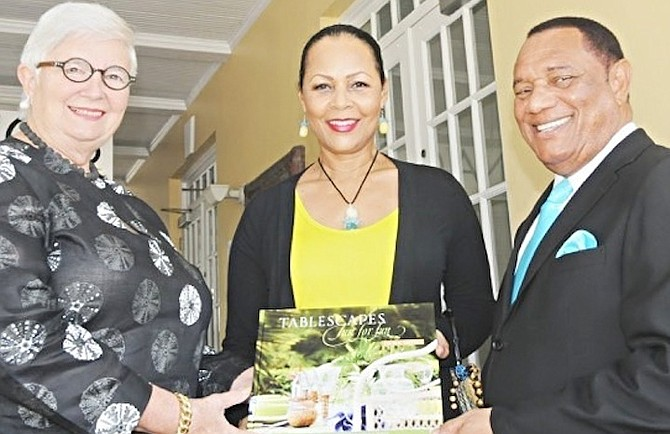 Art collector Dawn Davies presents a copy of her latest book TABLESCAPES: Just For Fun to Prime Minister Perry Christie and Bernadette Christie at the National Art Gallery of the Bahamas. 