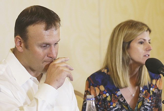Former Miami Dolphins fullback Rob Konrad, left, with his wife Tammy during a news conference where he told of his ordeal after he fell off his boat nine miles from shore while fishing last week off the South Florida coast. Inset right, Konrad in 2001 scoring for the Miami Dolphins.