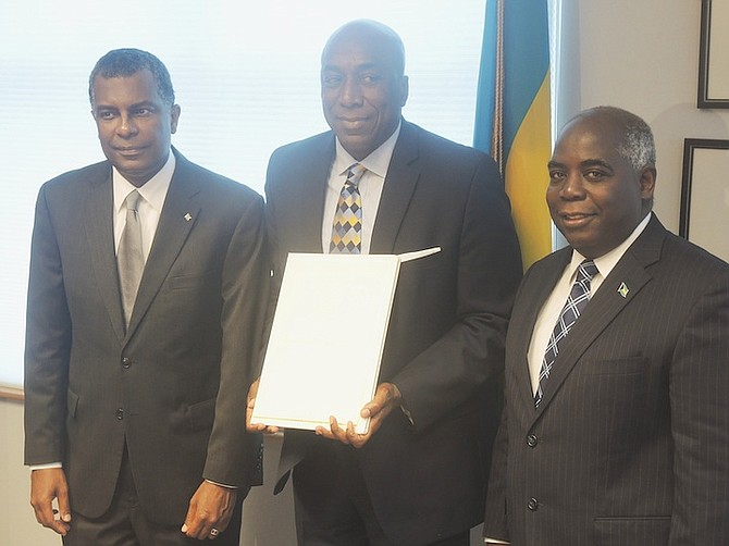 Lynden Rose, centre, the new Honorary Consul to Houston, flanked by Minister of Foreign Affairs Fred Mitchell, left, and Deputy Prime Minister Philip Davis.