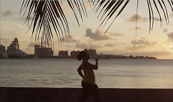 An image from the Stronger Bahamas video showing a woman jogging in Nassau. A male model featured in the video has complained that the pay was less than $100 for a two-day shoot and said he felt he was not informed of the true nature of the campaign before or after the production.