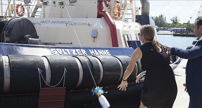 Hanne Helweg, the wife of Martin Helweg, managing director of Svitzer, breaks a ceremonial bottle of champagne on the bow of the refurbished tugboat, Svitzer Hanne. Photo: Dave Mackey