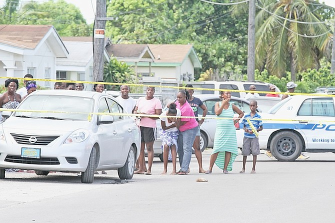 A family member is consoled at the scene of yesterday's shooting of a young man in Nassau Village.