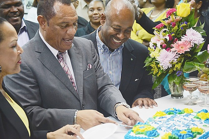 Minister of Tourism Obie Wilchcombe pictured with Prime Minister Perry Christie earlier this year, cutting a cake to celebrate Mr Christie's 40 years in public service. 