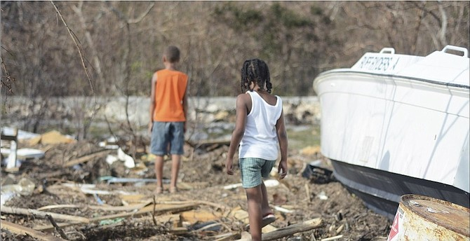 Youngsters on Long Island yesterday exploring the wreckage following Hurricane Joaquin. 