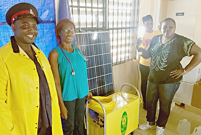 Local nurses with the solar powered generator that will allow medical supplies such as insulin to be refrigerated as well as power the airport terminal.