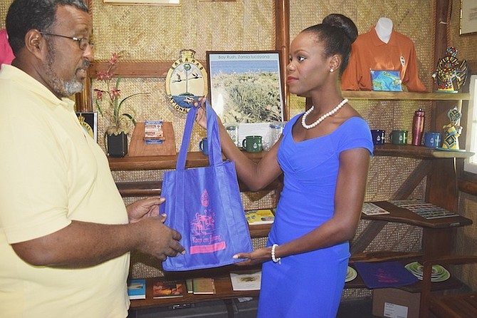 Miss Earth Bahamas Darronique Young receives a BNT shopping bag from director Eric Carey.