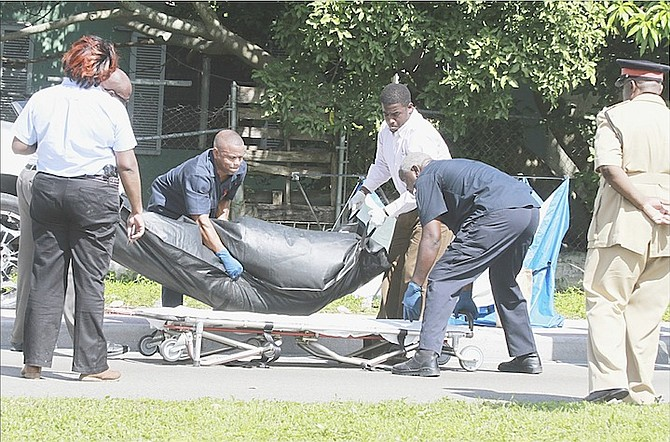 The body of a man is removed from the scene of a shooting on Tonique Williams Darling Highway yesterday. Photo: Tim Clarke/Tribune Staff