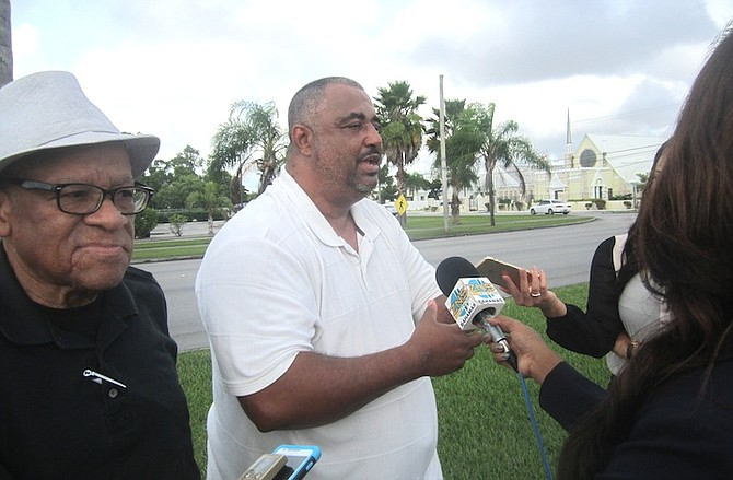 Troy Garvey reports to the media after his meeting with the Grand Bahama Power Company, watched by Etienne Farquharson. Photo: Denise Maycock/The Tribune