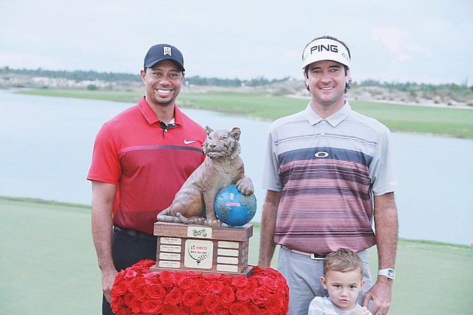 HERO WORLD CHALLENGE champion Bubba Watson and his son Caleb, share a special moment with tournament host Tiger Woods.