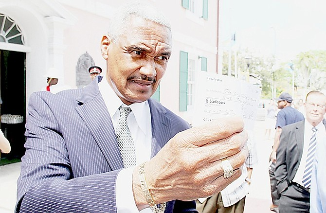 LESLIE Miller pictured last year showing the cheque for $1,000 he said he was giving to the Bahamas Crisis Centre after he had said in the House of Assembly that he had physically abused an ex-girlfriend, something he later said was a joke. The centre declined the offer of a cheque from Mr Miller.