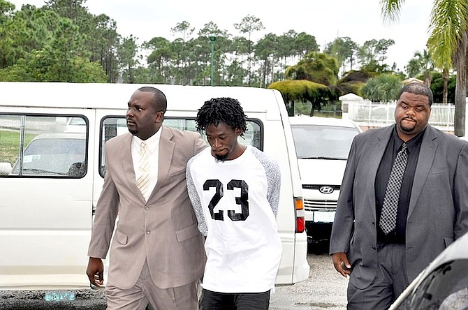 Philip Sweeting being escorted outside Freeport Magistrate's Court yesterday. Photo: Vandyke Hepburn