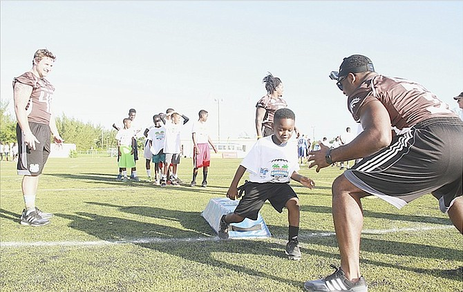 DOZENS of youth take part in various drills by the USA Football staff players during a Youth Football Leadership Clinic at the Roscow Davies Soccer Field yesterday.                                                                                                                                                                                                                                                                  Photo by Tim Clarke/Tribune Staff