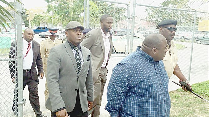 Akiel Smith (brown suit, light shirt, centre) and Carl Smith (blue shirt) outside court.
