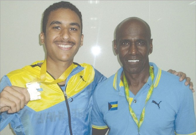 BENJAMIN NAJMAN shares a special moment with coach Michael Armbrister after winning gold in the 5,000 metres.