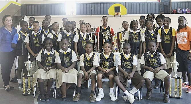 SKY IS THE LIMIT: Vice principal Deborah Burrows (far left) and head coach Nekeno Demeritte (far right) with members of their Temple Christian Academy Suns boys and girls basketball teams as they display their trophies won this year. 