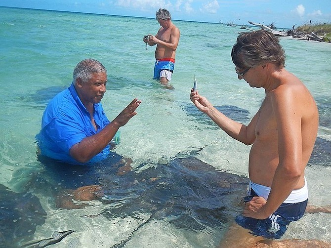 Keith Cooper, left, pictured during one of the tours that he operates to allow people to encounter stingrays.
