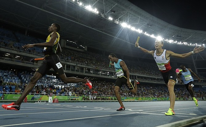 Chris Brown, of the Bahamas, crosses the line in third place behind Jamaica's Javon Francis and just ahead of Belgium's Kevin Borlee in the men's 4 x 400m relay final on Saturday night (AP)