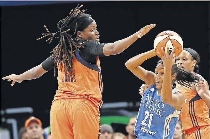 Minnesota Lynx's Renee Montgomery (21) tries to pass the ball behind Connecticut Sun's Jonquel Jones, of the Bahamas, during the first half of a WNBA game on Sunday in Minneapolis.       (AP Photo/Stacy Bengs)