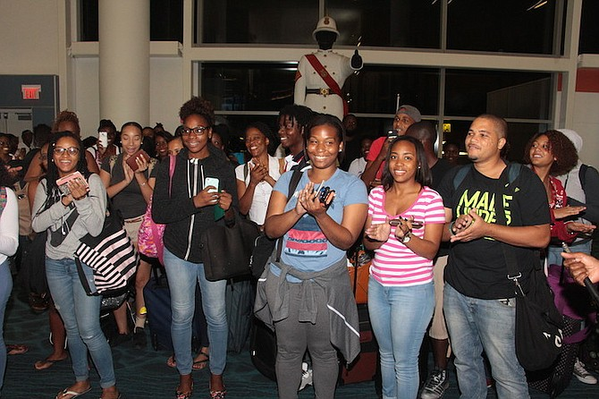 Happy Bahamian students back at Lynden Pindling International Airport on Saturday night after being brought home by Bahamasair from Jamaica, which is threatened by Hurricane Matthew. Photo: Eric Rose/BIS