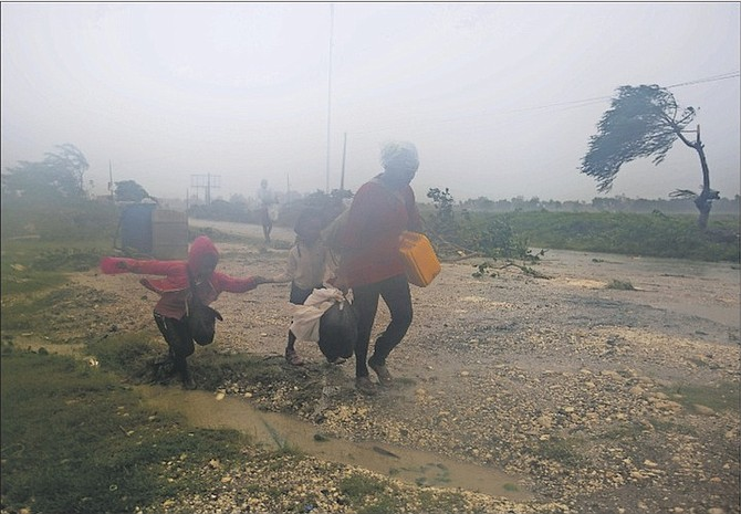Residents head to a shelter in Leogane, Haiti, yesterday. Matthew slammed into Haiti's southwestern tip with howling, 145 mph winds, tearing off roofs, uprooting trees and leaving rivers bloated and choked with debris.  Photo: Dieu Nalio Chery/AP