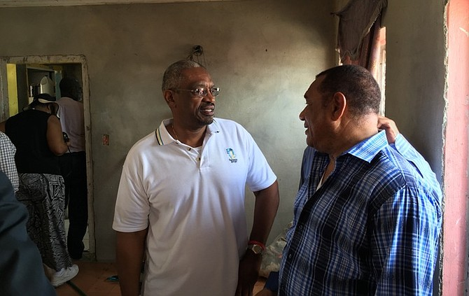 Standing in a damaged home in Lowe Sound, North Andros, Dr Hubert Minnis and Prime Minister Perry Christie share concerns over the massive destruction caused by Hurricane Matthew during an assessment trip on Saturday. Photo: NEMA