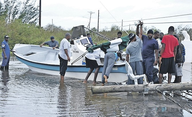 A boat in the middle of a road in Grand Bahama amid downed power lines and flood water, as residents start to clean up. 
