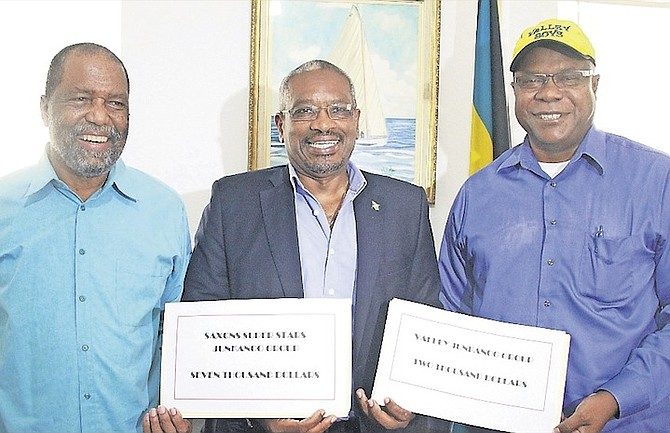 FNM Leader Dr Hubert Minnis donating money yesterday to the Shells Saxons Super Stars, represented by leader Percy Vola Francis, left, and Valley Junkanoo Group chairman Brain Adderley.