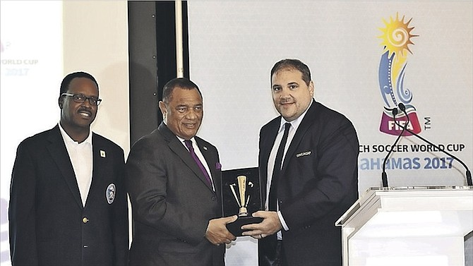 CONCACAF President Victor Montagliani makes a special presentation to Prime Minister Perry Christie after announcing that The Bahamas will host the 2017 CONCACAF Beach Soccer Championships in February. Minister of Youth, Sports and Culture Dr Daniel Johnson looks on.