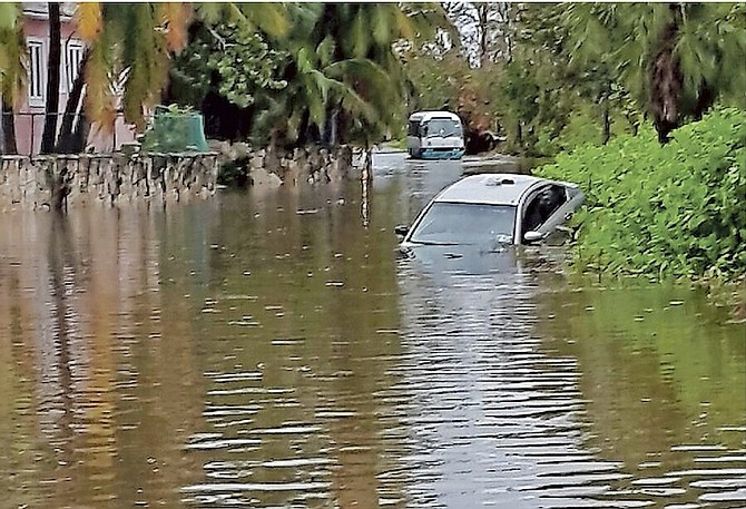 Flooding on West Bay Street yesterday leaves one car very much the worse for wear after it is almost submerged as waters rose following torrential rainfall. The scene pictured is near the Sun Fun resort, and the airport road was reported to be almost impassable.