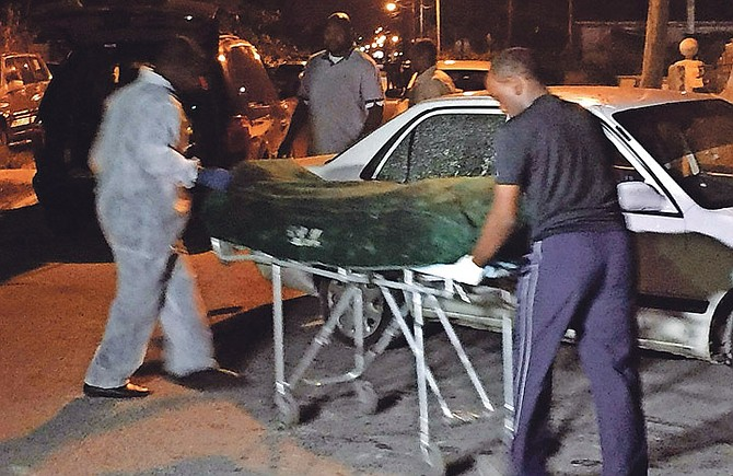 Police remove the body of the victim from the scene.