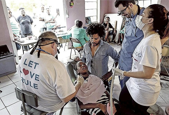 Musician Lenny Kravitz looks in as a youngster gets a dental check-up from a team in partnership with the GLO Good Foundation. Photo: Mathieu Bitton