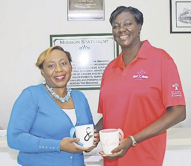 Entrepreneur Gina Smith (left) and Laverne Wildgoose of the Cancer Society of the Bahamas hold up the 'Mugs for the Cure'.