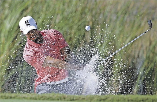 TIGER WOODS hits from a bunker onto the sixth green during the Pro-Am at the Hero World Challenge golf tournament yesterday at the Albany Resort in Nassau, Bahamas. 