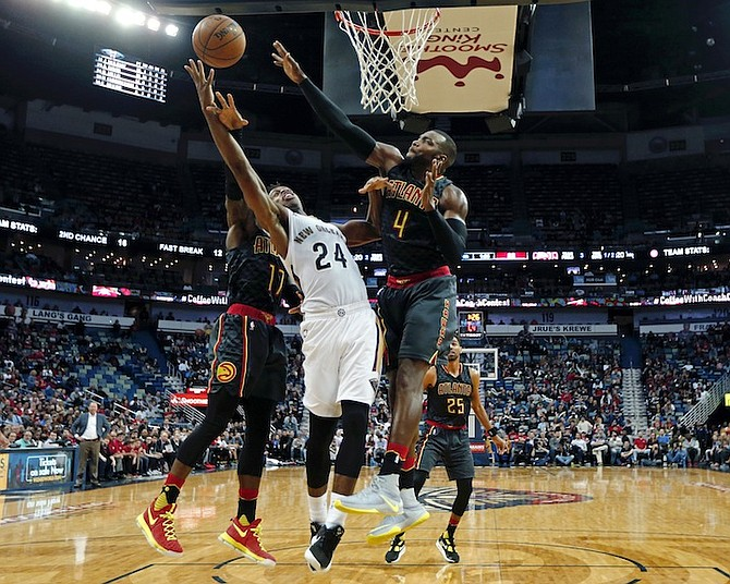 New Orleans Pelicans guard Buddy Hield (24) goes to the basket against Atlanta Hawks guard Dennis Schroder (17) and forward Paul Millsap (4) in the second half of an NBA basketball game in New Orleans, Thursday, Jan. 5, 2017. The Hawks won 99-94. (AP Photo/Gerald Herbert)