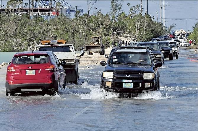 Cars splashing through the flood water on Fishing Hole Road.