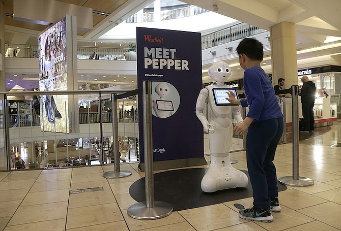 A boy plays with Pepper the robot at Westfield Mall in San Francisco. (AP)